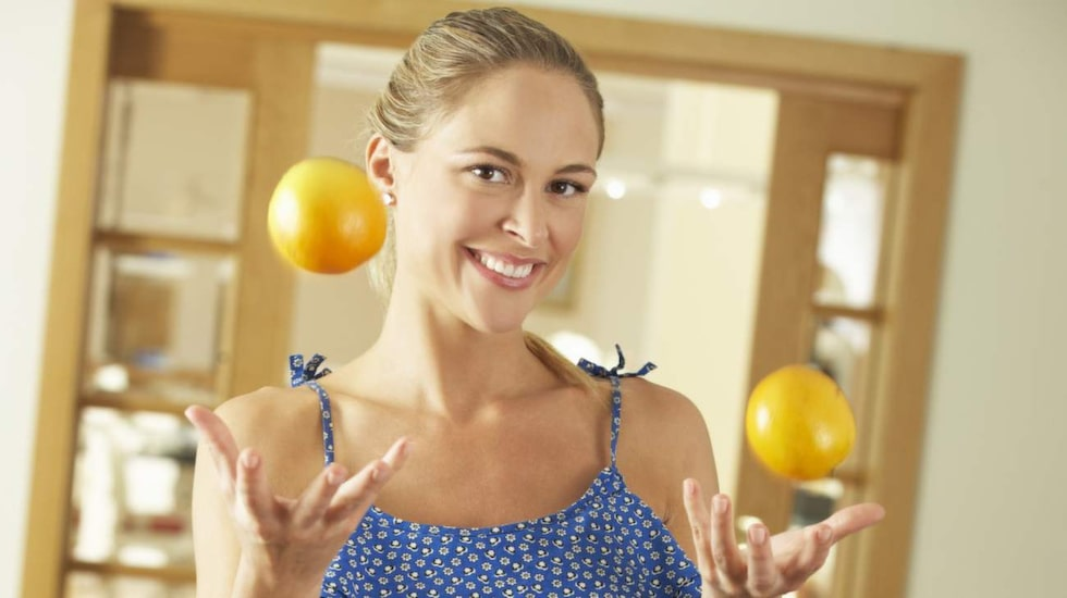 woman sitting on kitchen counter throwing orange in the air