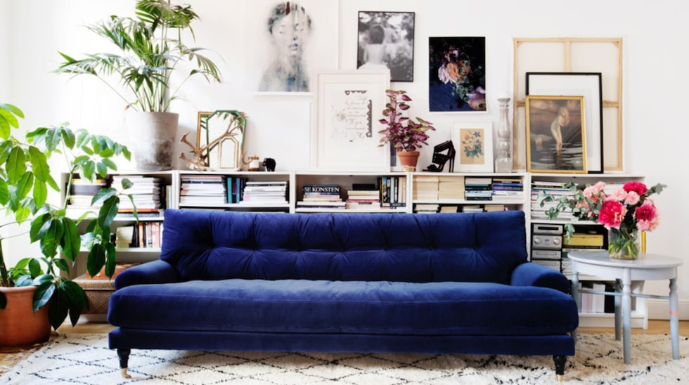 Snyggt stilleben med uppsatta tavlor och ramar som får vila på en låg bokhylla hemma hos stylisten Amelia Widell.