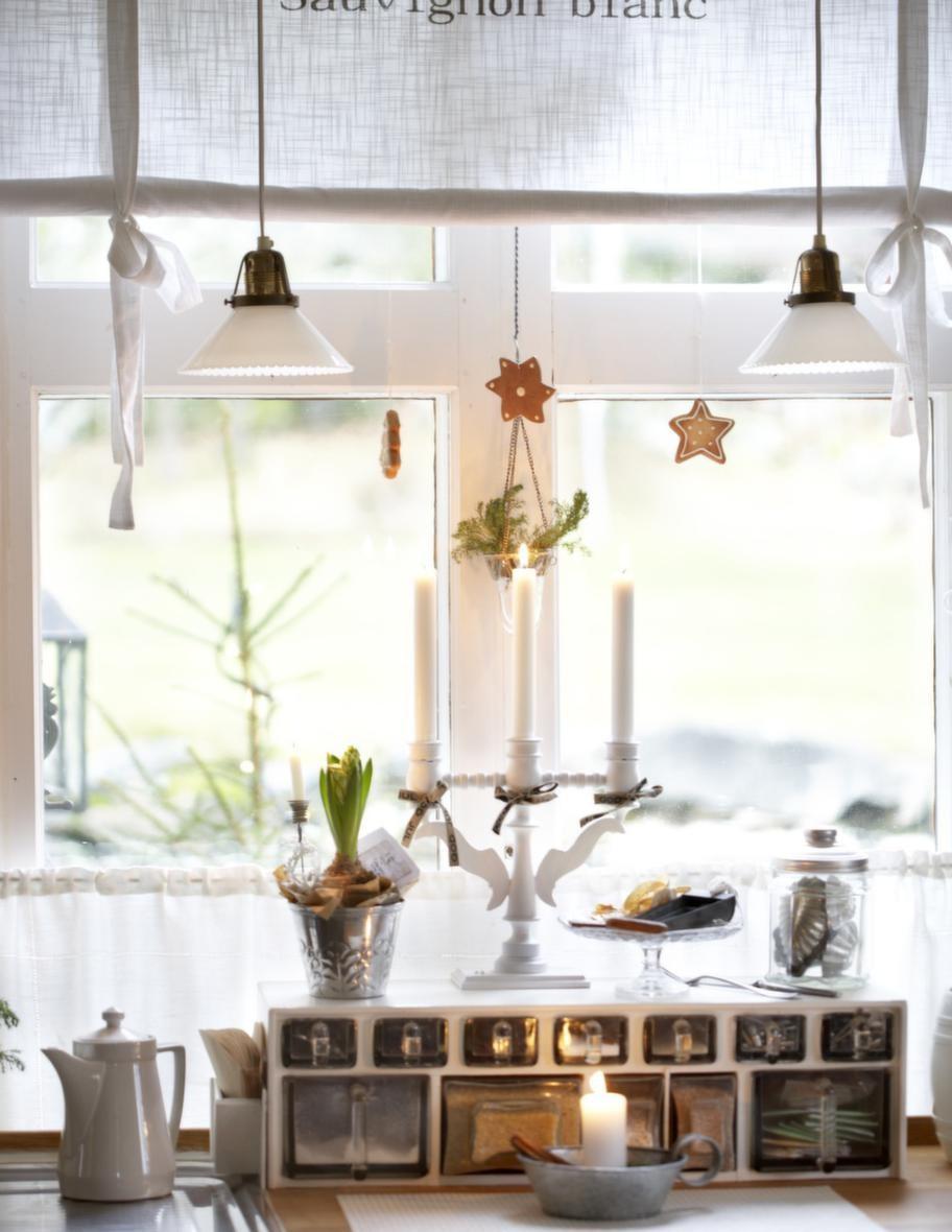 I FÖNSTRETMed pepparkakor på snöre och julblommor skapar Tarja jul. Den fina träljusstaken har hängt med i många år.