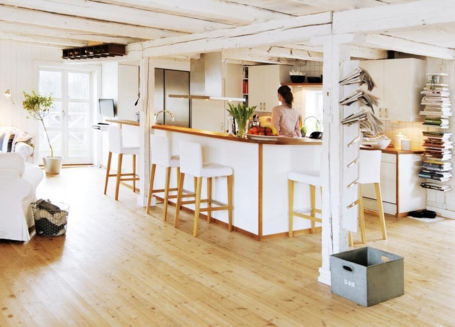 Öppna rumPlanlösningen är öppen och luftig. De gamla bärande bjälkarna är vitmålade och det kraftiga björkgolvet ger en rustik känsla. I takhöjd hänger en handskhylla från 30-talet som fyndats på loppis. Den har tillhört Göteborgs konserthus, nu används den som vinställ.