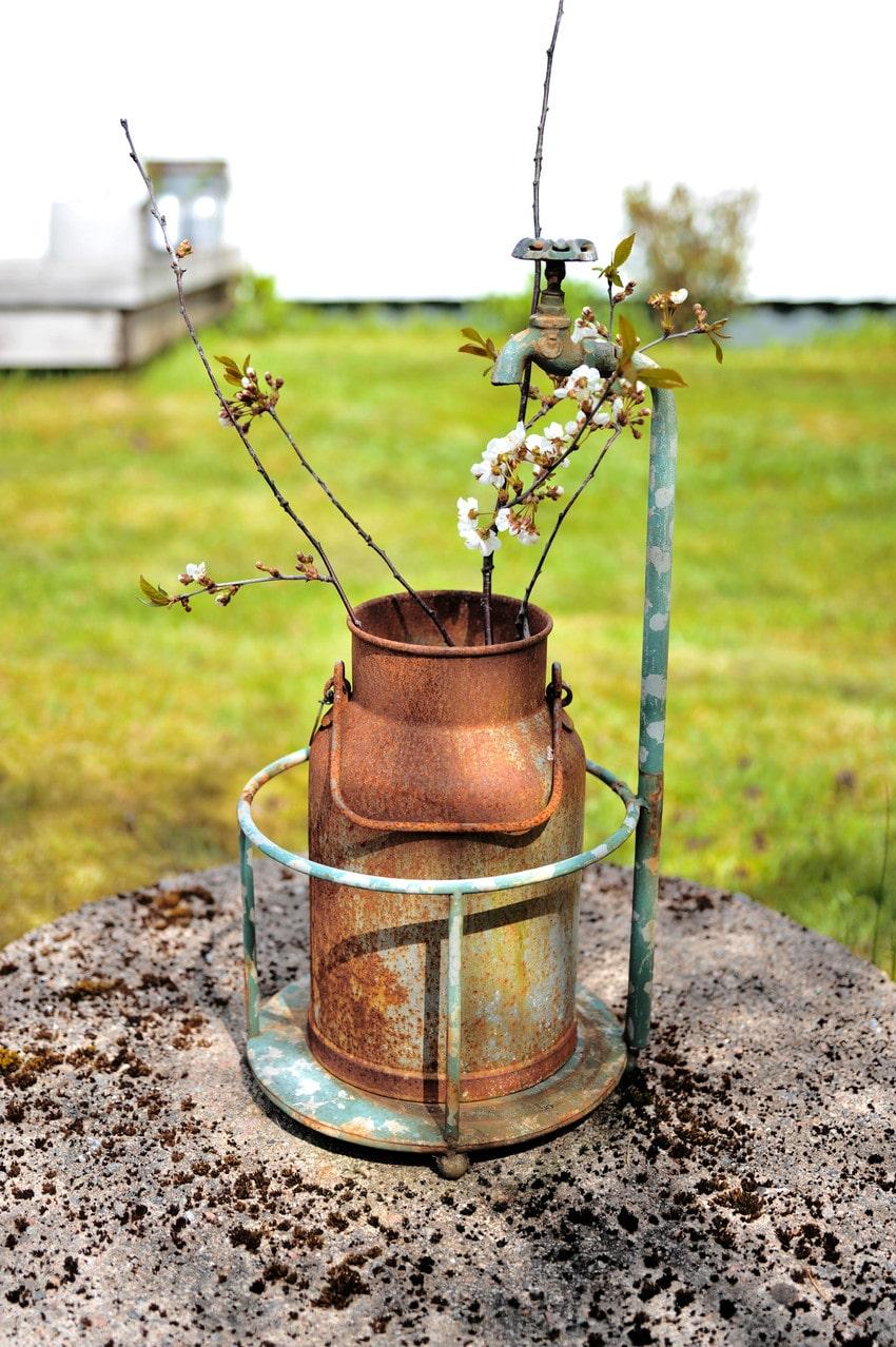 Den gamla brunnen ger vatten till blommorna och pryds av en loppisfyndad mjölkkanna.