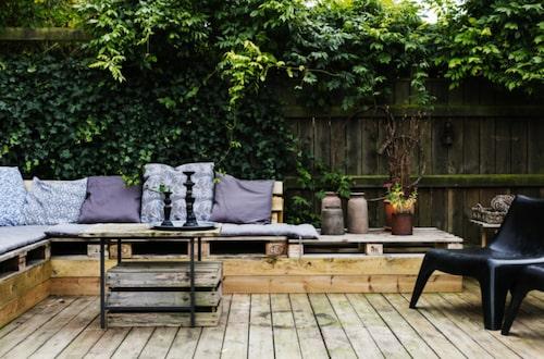 Trären lounge. På terrassen finns en mysig loungehörna som används långt in på hösten. Både soffan och bordet har Malin och Stefan gjort själva. Ljusstakarna kommer från Enkla ting. Svarta fåtöljer från Ikea.
