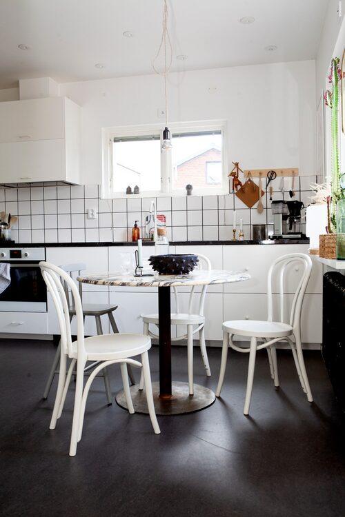 Modernt och enkelt i köket. Loppisfyndade stolarna Öglan, ursprungligen från Ikea. Bordet är tillverkat av Johannes. Kök från Ikea och bänkskiva från Ryssby kök. Knopplist från Korgboet, apa av Kay Bojesen och ljusstake på bord, Hay.