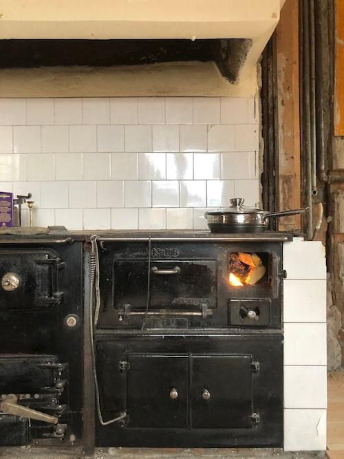 Till dess att köket är klart och den nya spisen installerad lagar de mat på vedspisen. Det vita kaklet i halvförband är troligtvis från 30-talet och precis vad Emilia önskade sig i sitt kök.